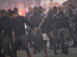 Police move a couple of handcuffed, recently detained men at Pavao Pavaozinho slum during a police operation in Rio de Janeiro, Brazil, Monday, Oct. 10, 2016...