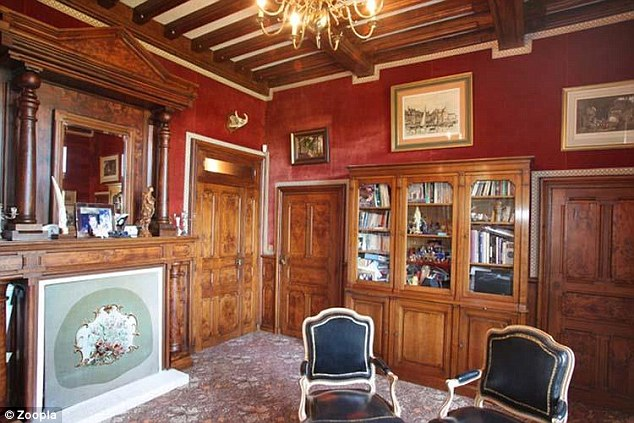 The impressive interior of the chateau includes wooden paneled doors and wooden beams on the ceilings
