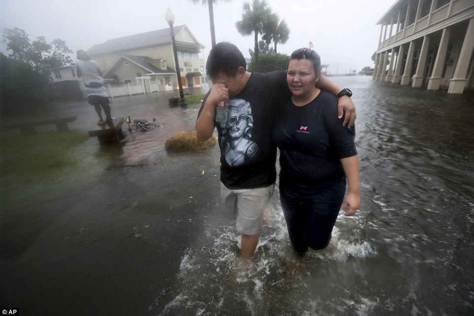 Local residents Michael & Tori Munton make their way through the flooded streets of downtown historic Saint Marys, Georgia, as the state and the Carolinas were preparing for the worst