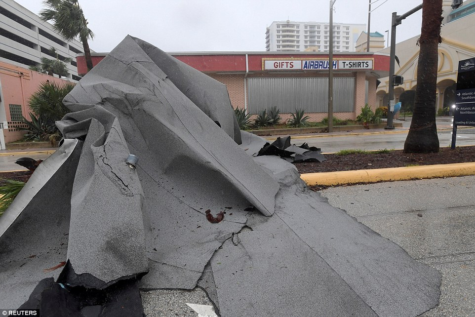 Crashed to earth: The roof of a nearby business lies on a street after the eye of Matthew passed by Daytona