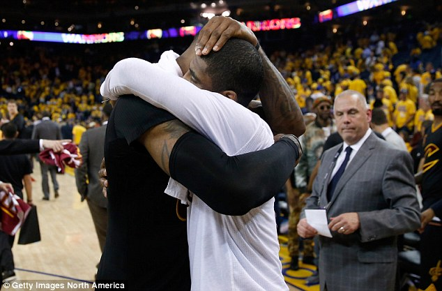James (left) and Kyrie Irving (right) embrace after forcing Game 6 with a victory at the Oracle Arena