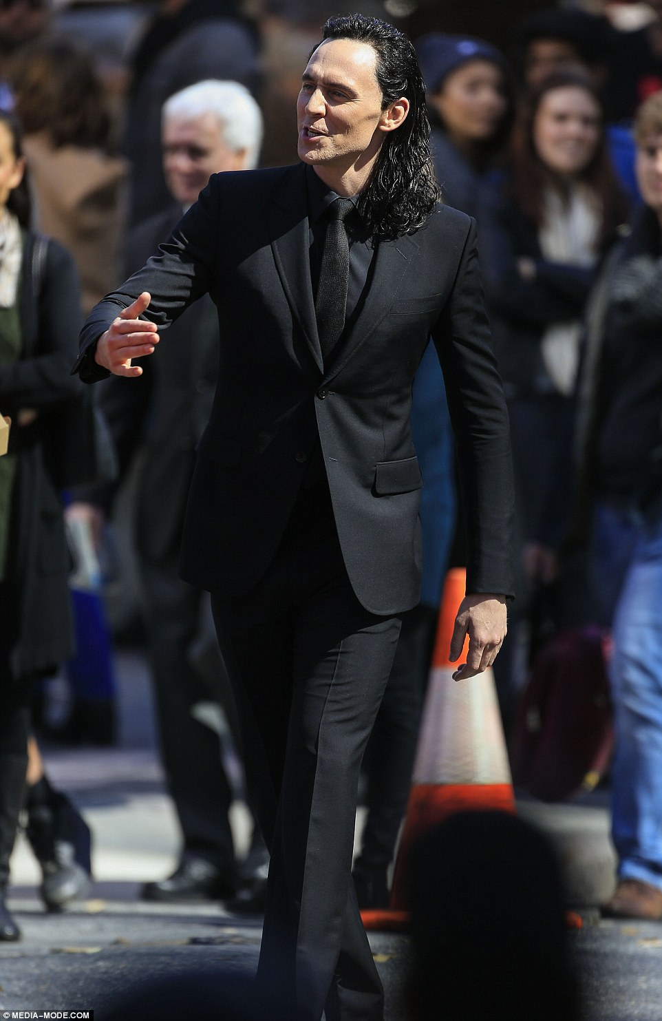 In his stride: Tom looked in his element as he strolled happily down the set while cameras rolled