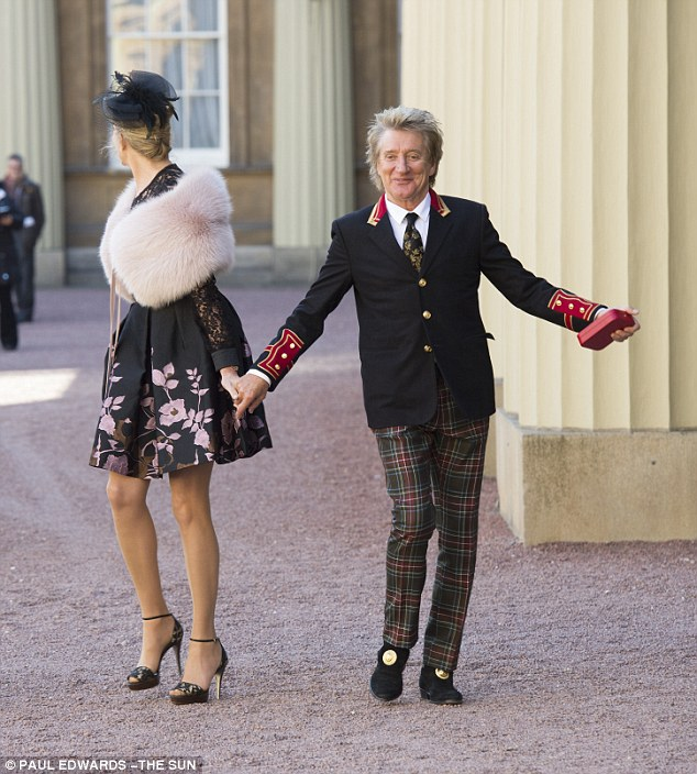 Oooh la la: Rod strikes a pose clutching his medal as he leaves the Palace with Penny