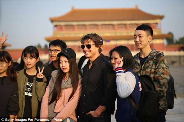 Making friends: The Hollywood star happily posed for photos with some lucky Chinese fans