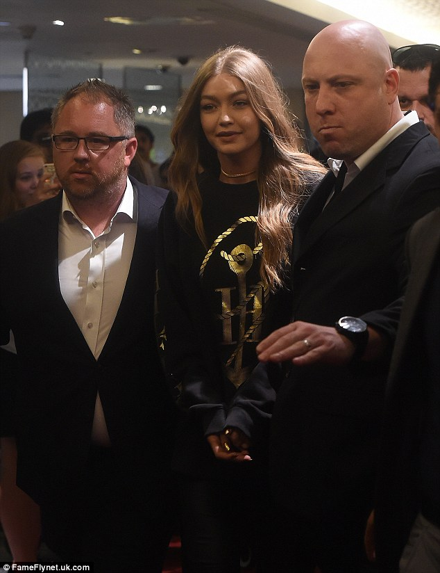 Flanked: Gigi Hadid was surrounded by security as she was helped through Dubai mall on Monday