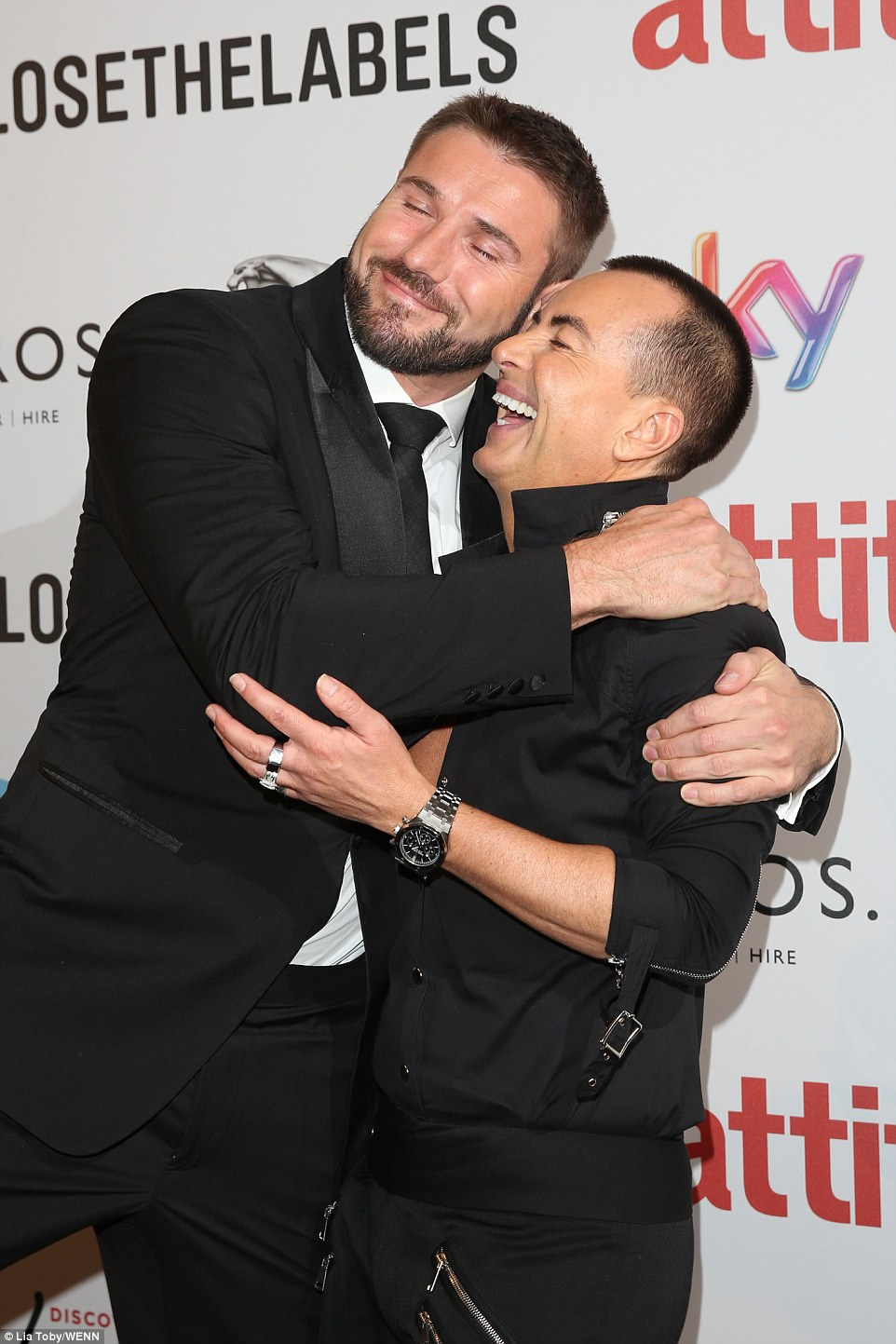 Cuddles: Ben Cohen snuggled up to fashion designer Julien McDonald as they both hit the red carpet in slick black ensembles