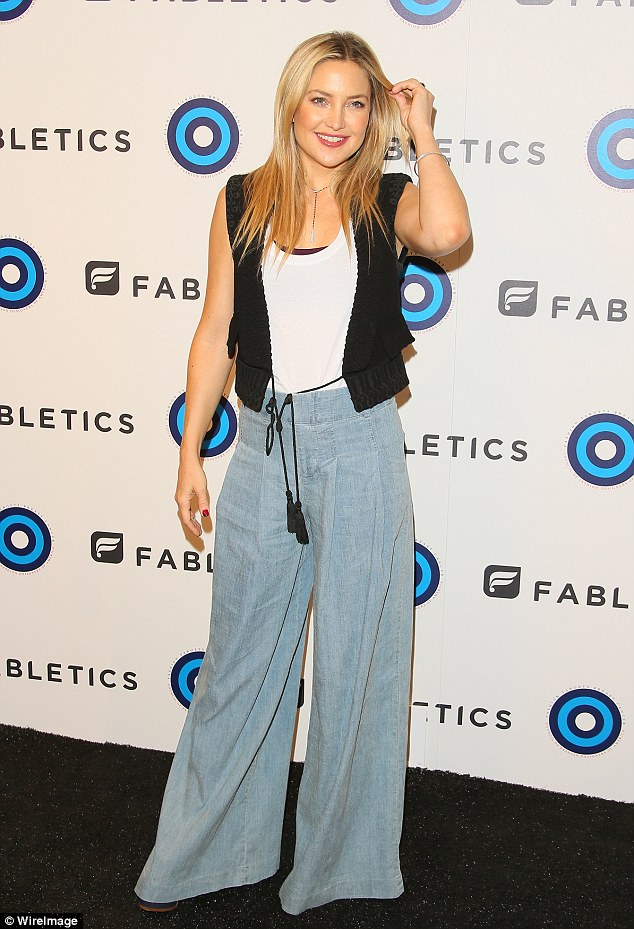 Lovely lady: The 37-year-old actresslooked groovy as she sported a black knit vest over a white sleeveless top