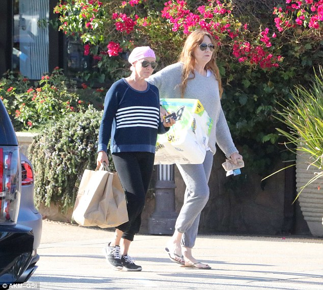 Doing her part: The 45-year-old actress managed to carry two shopping bags out of the store while her mom lugged a large package of paper towels