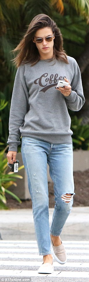 Keeping it cool: She wore a grey crewneck sweater as she paired the top with a pair of ripped skinny jeans and tan slip-on shoes