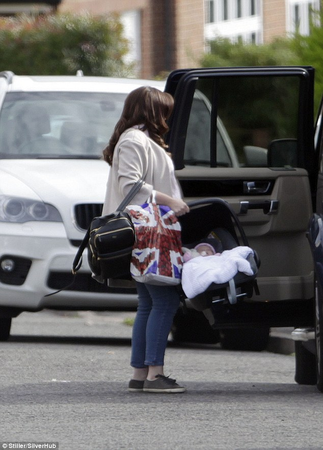 Mother and daughter: She opened the back door of her black 4x4 and carefully removed Joanie Elizabeth's car seat