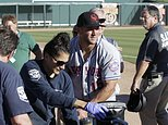 Scottsdale Scorpions outfielder Tim Tebow, center, comforts a fan, on ground, who was suffering a seizure, following Tebow's debut against the Glendale Desert Dogs in a baseball game Tuesday, Oct. 11, 2016, during the Arizona Fall League in Glendale, Ariz. The Phoenix Fire Department said a man in his 40s was having a seizure Tuesday at Camelback Ranch, the spring training home to two major league teams. (Rob Schumacher/The Arizona Republic via AP)