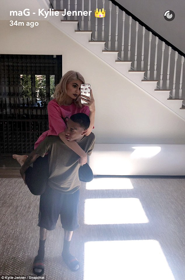 She's got his back: Kylie Jenner shared a clingy Snapchat alongside her beau Tyga on Wednesday from the spacious foyer of one of her magnificent Los Angeles mansions