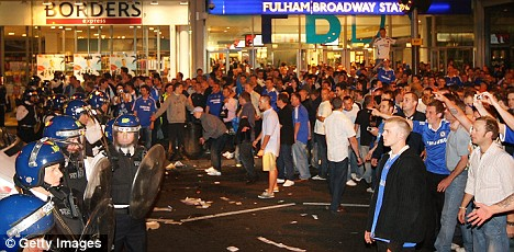 Police and fans face off outside Fulham Broadway tube station near Stamford Bridge after Chelsea's Champions League loss
