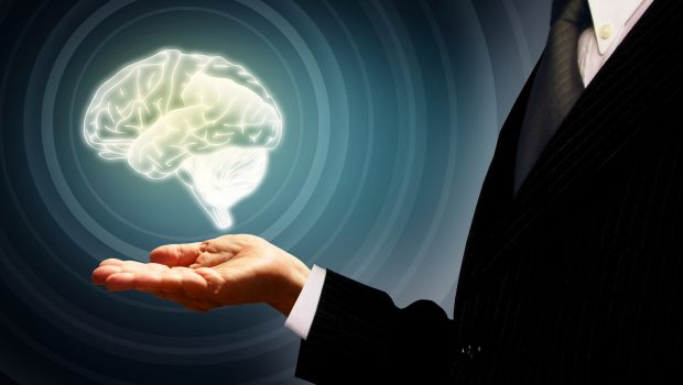 Businessman holding a virtual human brain in the palm - Skills, human development and IQ concept