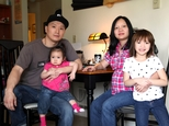 FILE - In this March 19, 2015, file photo, Korean adoptee Adam Crapser, left, poses with daughters, Christal, 1, Christina, 5, and his wife, Anh Nguyen, in the family's living room in Vancouver, Wash. After struggling with joblessness because of his lack of immigration papers, homelessness and crime, Crapser, a South Korean man who was flown to the U.S. 37 years ago and adopted by an American couple at age 3 has been ordered deported back to a country that is completely alien to him, Wednesday, Oct. 26, 2016.  (AP Photo/Gosia Wozniacka, File)