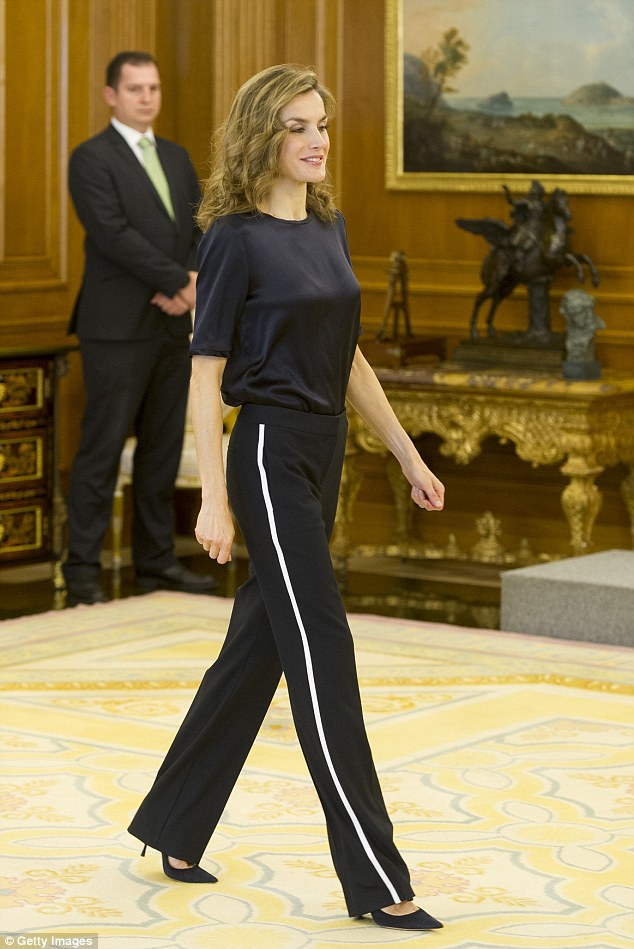 In the comfort of her own palace, Letizia ditched her usual chic look and opted for a plain black T-shirt twinned with black trousers, which had a sporty white stripe along the side seam