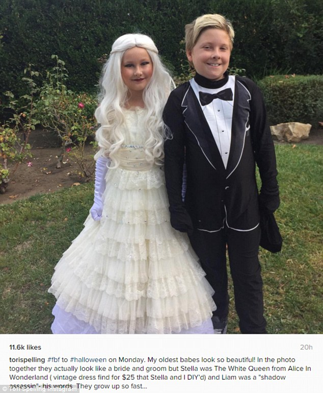 "'My oldest babies look so beautiful!': For her Flashback Friday, Tori Spelling posted an image of her eight-year-old Stella dressed as Lewis Carroll's White Queen and her nine-year-old Liam as 'a ""shadow assassin,""' though she admitted 'they actually look like a bride and groom'"