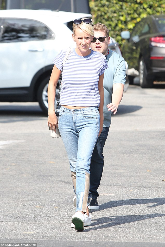Kiss-chase? Julia dressed down in a blue and white striped T-shirt and ripped jeans, opting for comfort in trainers
