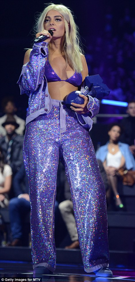 A touch of purple: Taking to the stage in a shimmering purple combo, teamed with a barely there bikini top of the same hue, the stunning singer paid tribute to the late rock icon, Prince.