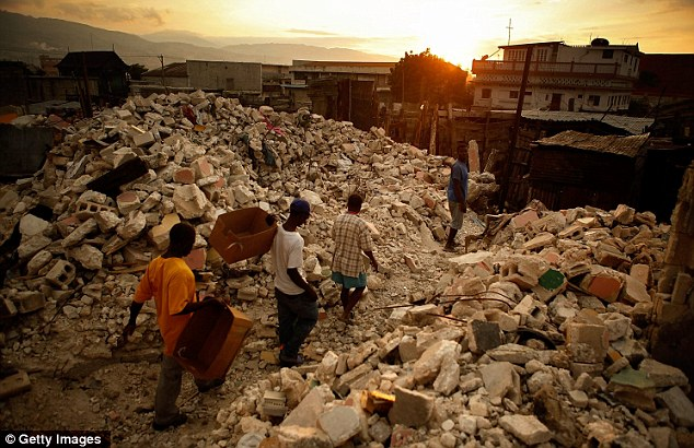 Devastation: Men attempt the massive clean up job following the earthquake which killed up to 300,000 people
