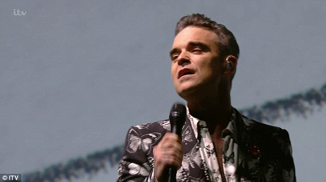 A pro: Appearing on the X Factor stage all alone in a spotlight, Robbie Williams looked nothing less than his usual enigmatic self as he sported a monochrome butterfly print suit