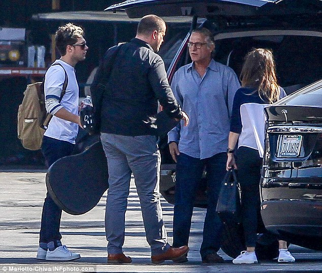 Group outing: Accessorising with a rucksack and sunglasses, he was spotted getting into a car with a mystery brunette- thought to be TV producer Ben Winston's wife Meredith- a good friend to Harry Styles