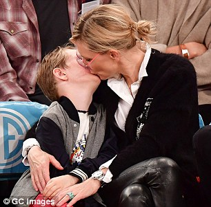 Doting mother: She then affectionately planted a kiss on his head during a quieter moment of the game
