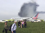 In this photo provided by passenger Jose Castillo, fellow passengers walk away from a burning American Airlines jet that aborted takeoff and caught fire on the runway at Chicago's O'Hare International Airport on Friday, Oct. 28, 2016. Pilots on Flight 383 bound for Miami reported an engine-related mechanical issue, according to an airline spokeswoman. (Jose Castillo via AP)