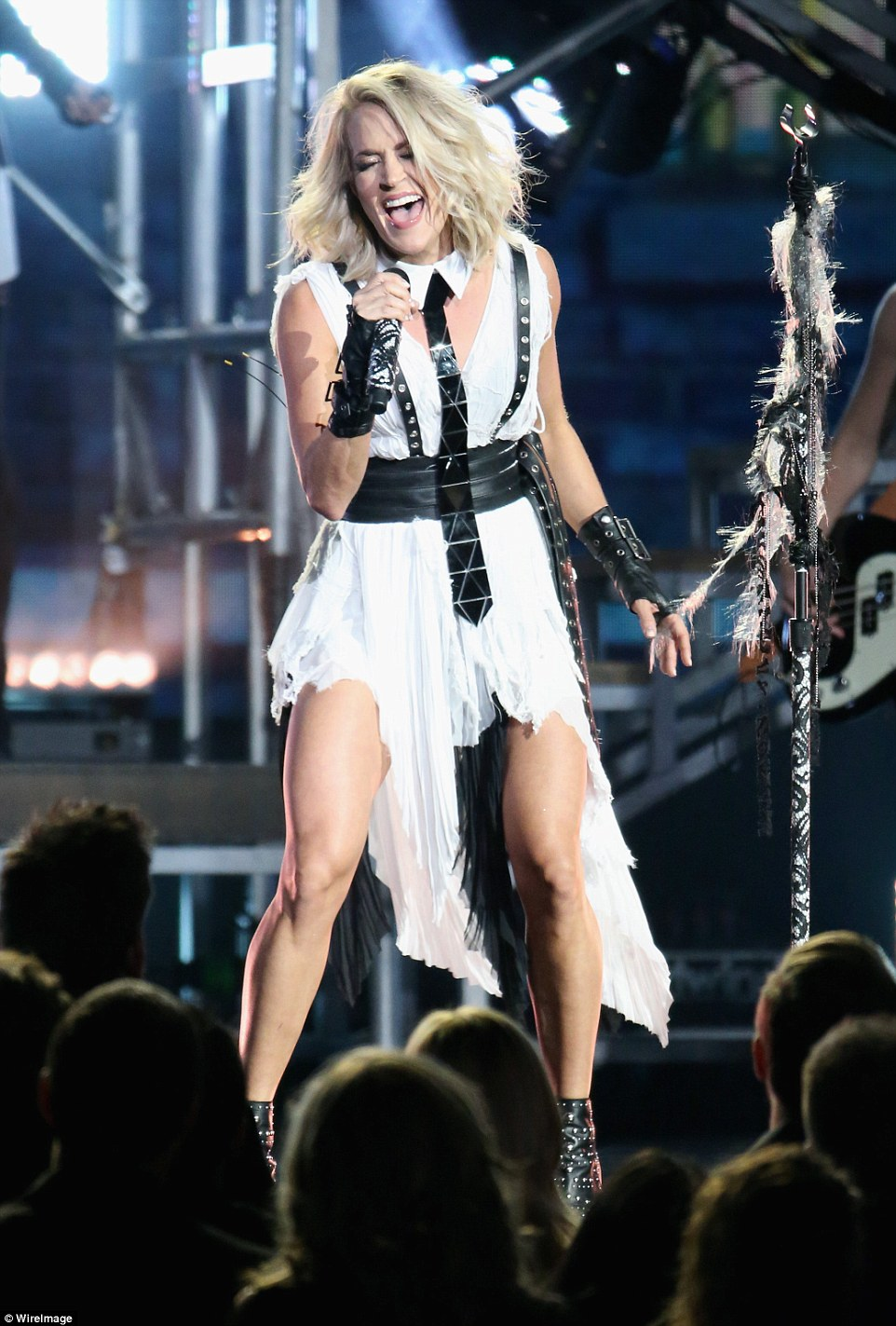 Racy: The outfit featured a black leather belt with matching suspenders, tie, large bracelets and studded leather boots