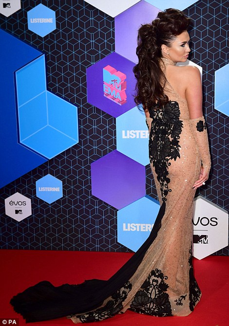 A little more demure:Charlotte Dawson sported a semi-sheer nude gown with embroidered black detailing and train