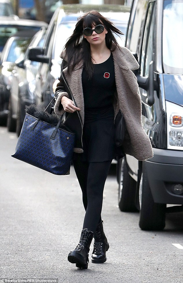 Looking good: The model sported a thigh skimming black dress and thick black tights