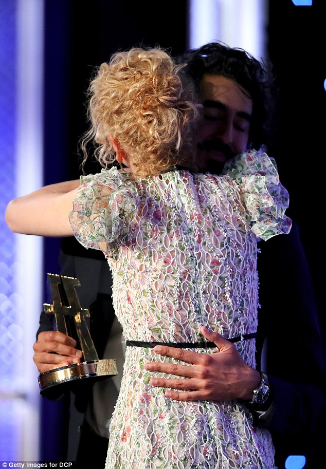 Hug it out: Dev wrapped his co-star in a warm embrace as he handed over the award