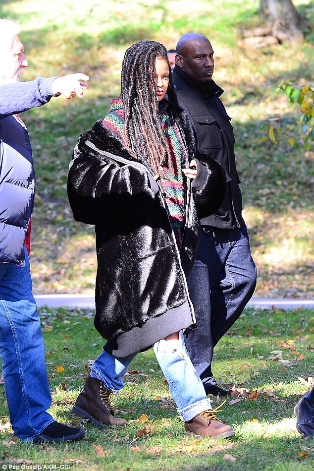 Big reveal: Rihanna slipped out of her heavy hoodie to show another, more brightly coloured hoodie underneath as her shot was set up in what looked like Central Park