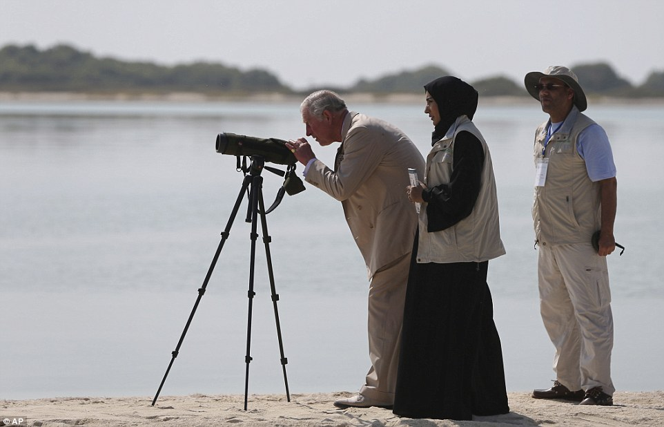 Prince Charles looks through a telescope as he visits Bu Tinah Island, at the center of the UNESCO Marawah Protected Marine Area on the Persian Gulf, about 105 miles, (170 km) west of Abu Dhabi, United Arab Emirates