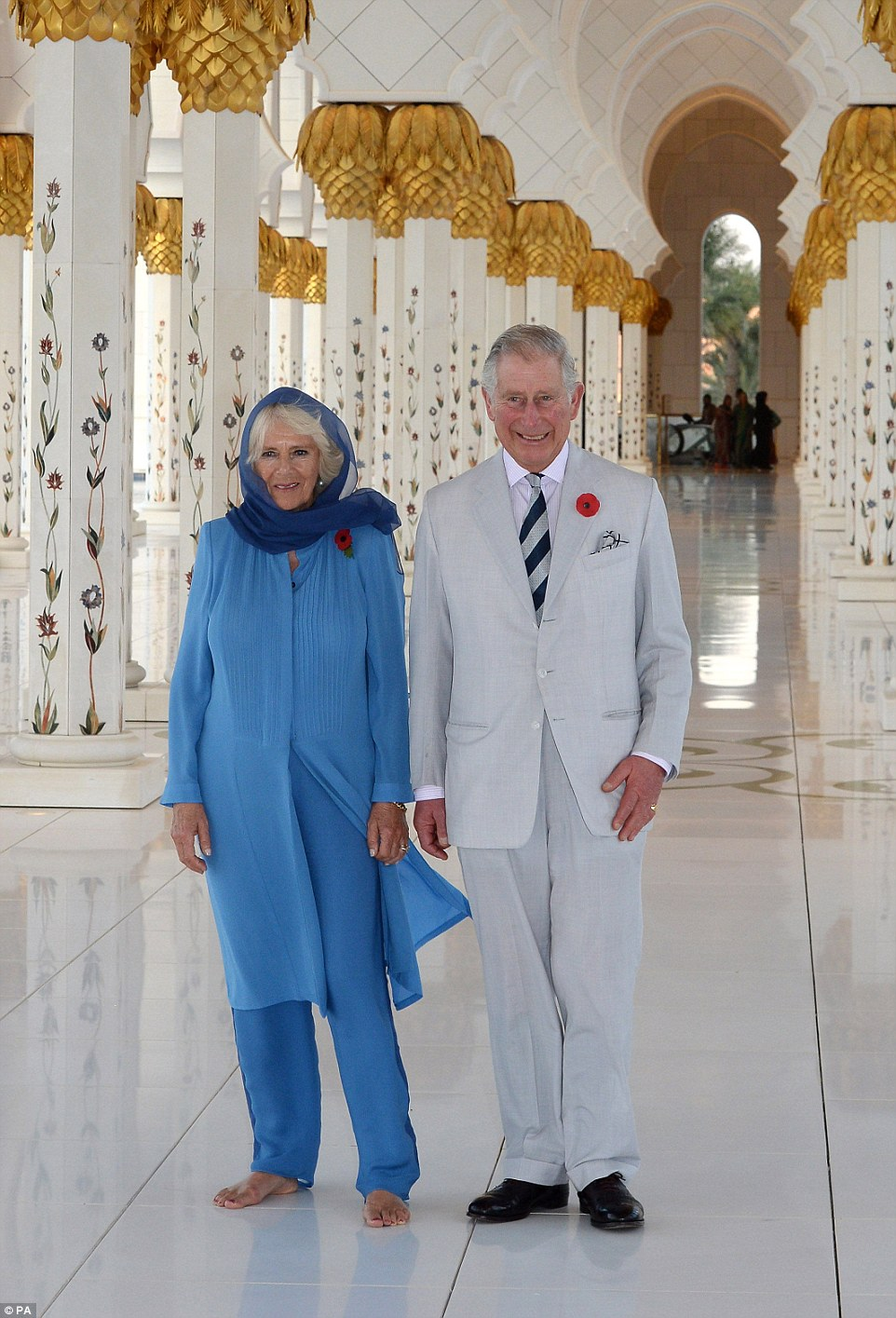 Prince Charles was dressed in a linen suit and striped tie, while Camilla wore a blue headscarf, long jacket and trousers