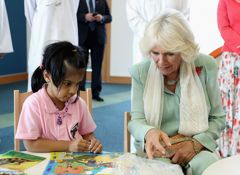 Helping hand! The Duchess gives her guidance to a young girl as she completes a jigsaw puzzle