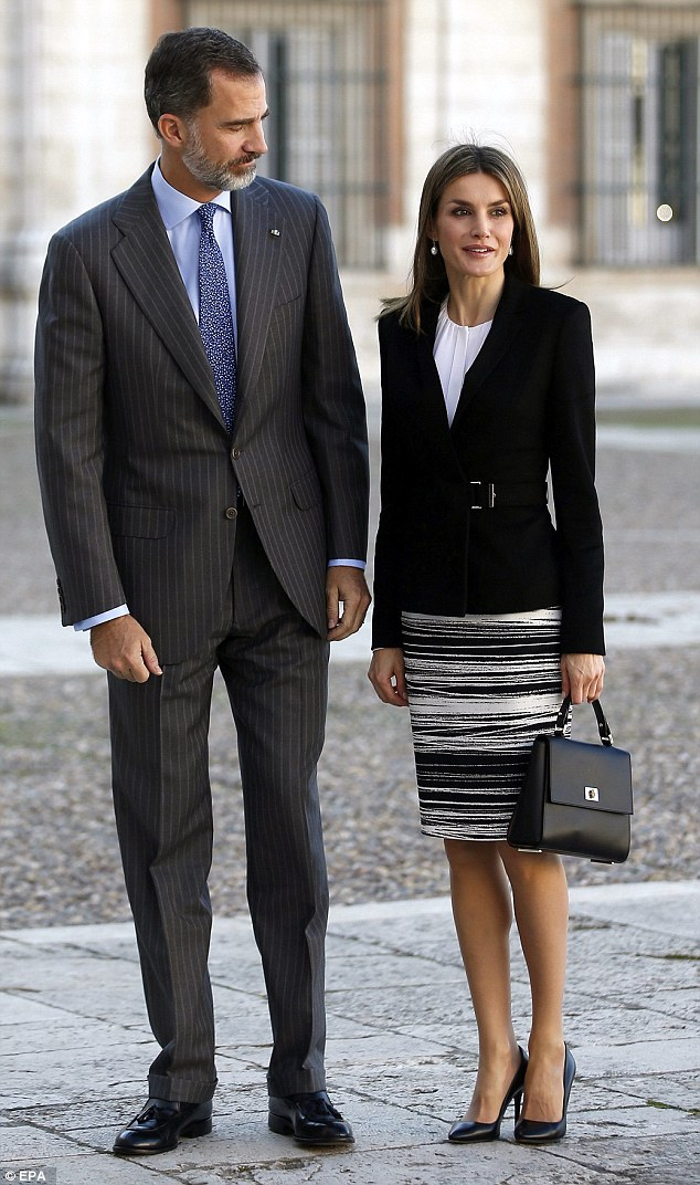 The proud king gives his wife an admiring glance as they arrive at an international symposium in Madrid