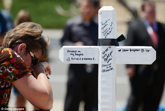 Prayer: Angie Terry pays tribute at the cross dedicated to one of the victims