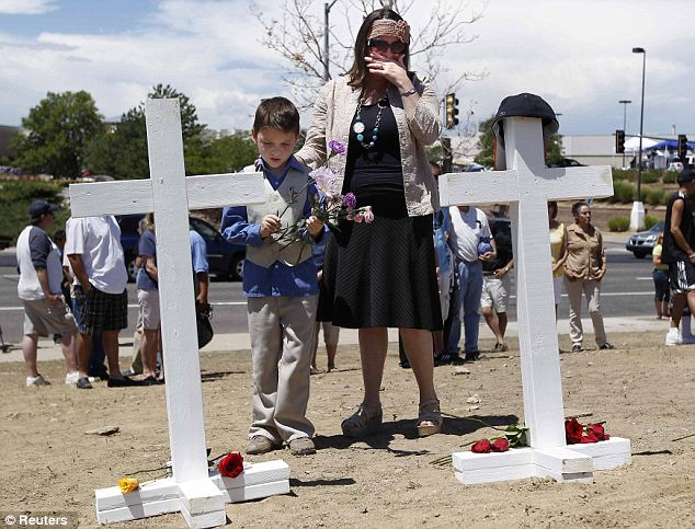 Paying tribute: Tamara Meza and her son Isaac place flowers in front of the crosses