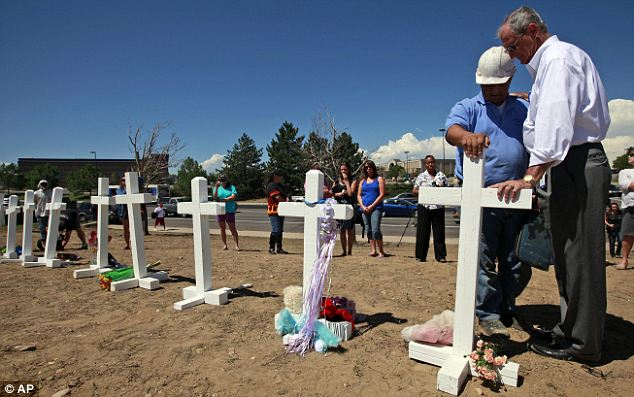 Public displays: Aurora Mayor Steve Hogan (right) says a prayer in front of one of the 12 crosses set up across the street from the movie theater in order to honor the victims