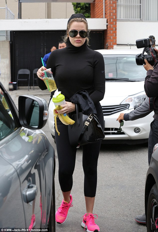 Earlier in the day: The Calabasas native covered her head as she exited her gym carrying two drinks and an eaten banana