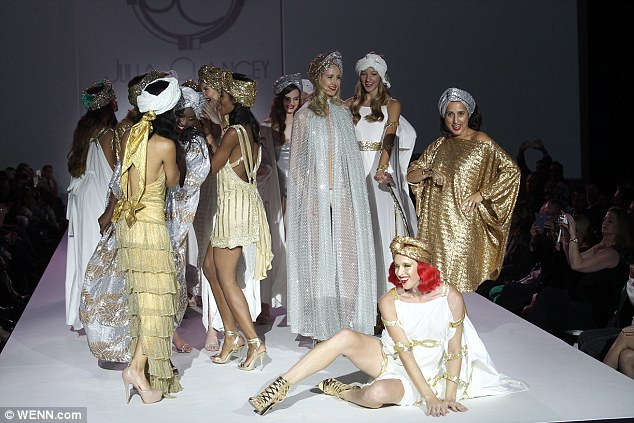 Strike a pose: The star was surrounded by models clad in gold and silver gowns