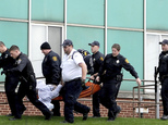 Emergency responders carry a person to an ambulance outside the Turtle Creek Valley Mental Health facility in Homestead, Pa., Friday, Nov. 11, 2016. Police officers shot an armed man inside a mental health facility after he stabbed several people and put down his knife but refused to drop his gun while his victims were bleeding badly, authorities said. (Pam Panchak/Pittsburgh Post-Gazette via AP)