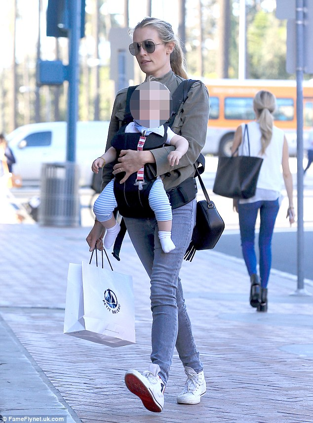 Always stylish: Despite carrying her adorable son in an baby carrier on her front, the So You Think You Can Dance host pulled of a fashionable dressed down look