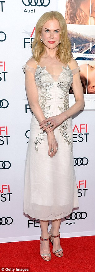 Changing it up: The star wore a cocktail length unusual white dress withstriking silver embroidered leaf pattern