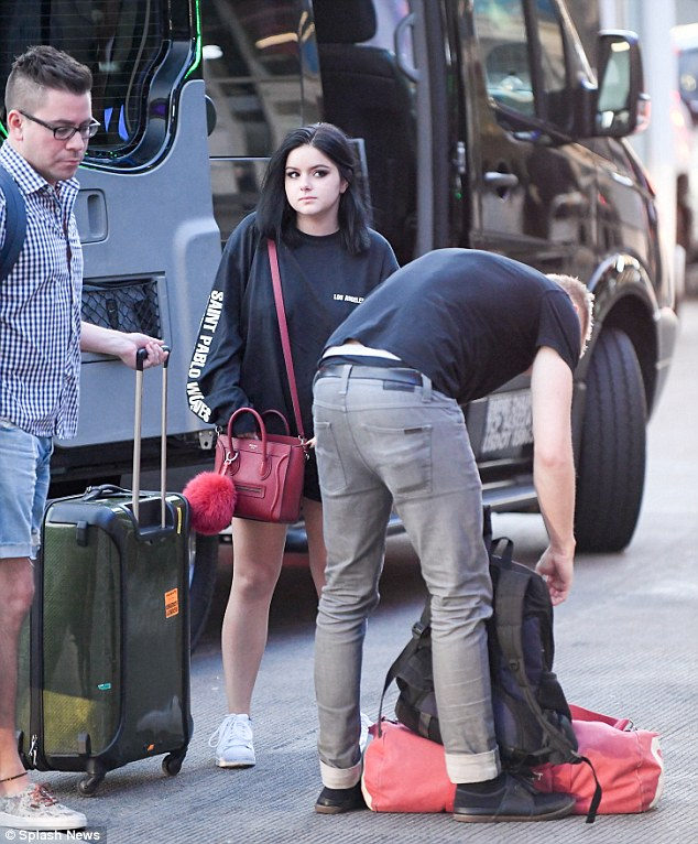 Jetting out together: Her friend fiddled with his rucksack and holdall as Ariel looked on