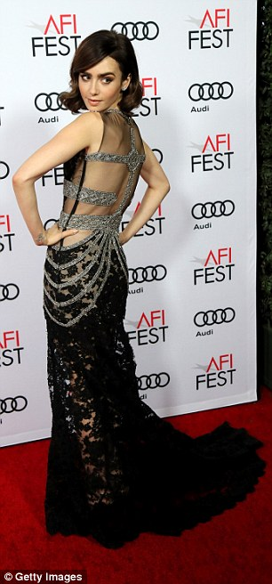 The daughter of musician Phil Collins appeared to be bra-free in the elaborate black lace 1920s inspired dress
