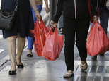 FILE - In this Sept. 20, 2016, file photo, women walk with plastic bags through Chinatown in San Francisco. California voters have narrowly approved a statewide ban on single-use plastic carryout bags. Proposition 67 was placed on the November 8, 2016, ballot by plastic bag industry supporters to try to overturn a ban approved by the state legislature two years ago. (AP Photo/Eric Risberg, File)