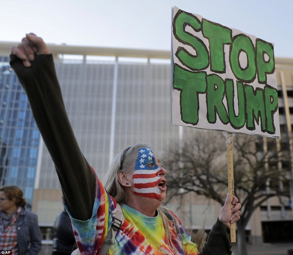 A demonstrator who painted her face in the colors of the American flag holds up a sign heading, 'Stop Trump', in Kansas City on Saturday