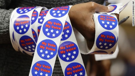 Iris Pettigrew carries voting stickers for voters after they cast their ballots on Tuesday, November 8, 2016, in Indianapolis.